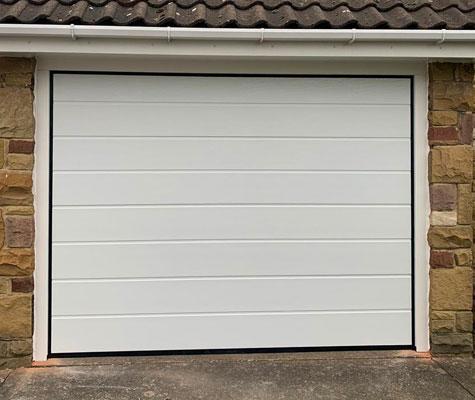 White garage door brown brick modern contemporary new Wakefield